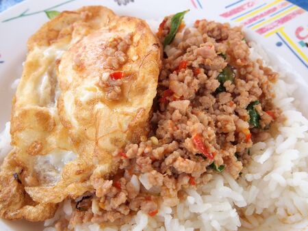 stir up: Close up Rice topped with stir fried pork and basil