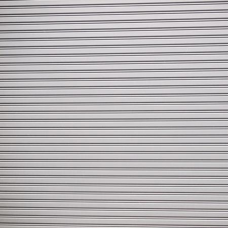shutter door: Illuminated grunge metallic roller shutter door Stock Photo