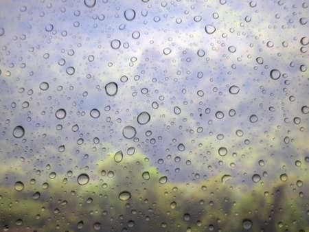 close up drops of rain on glass background. mountain out of focus