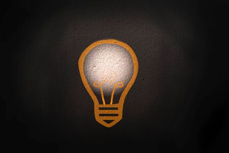 Abstract thinking light bulb on black concrete wall background