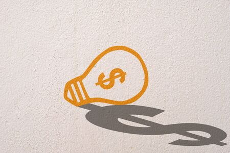 Abstract orange thinking light bulb and dollar shadow on concrete wall background
