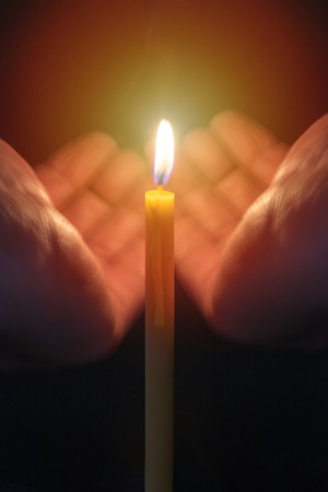 hands holding burning candle from wind and pray