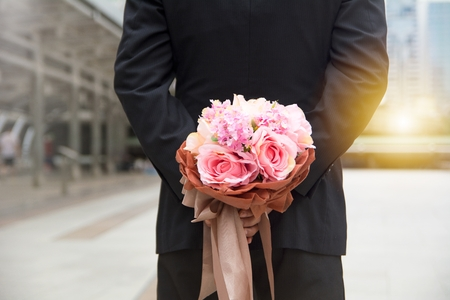 Man holding bunch of flower behind the back during valentine time