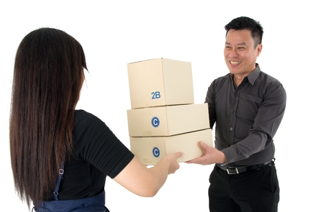 Lady handing over a stack of package with special service to a happy businessman isolated on white background