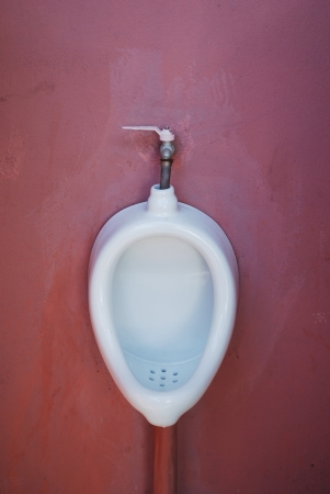 Urinal on dark pink wall photo