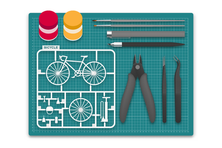 Plastic model with tool kit on cutting mat, bicycle concept design illustration isolated on white background with copy space