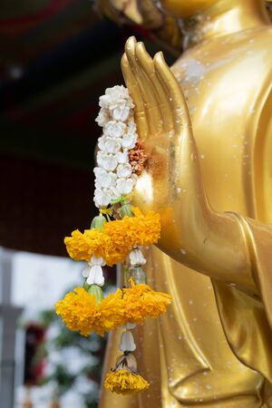 Close up Hand of The Buddha statue gold color hold flower garland in temple at thailand Imagens