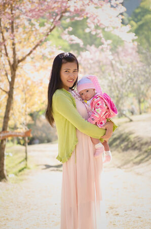 Mother with baby at outdoors in spring blooming garden photo