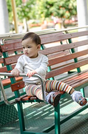 Portrait of little baby boy sitting on wooden bench in park  in thailand. photo