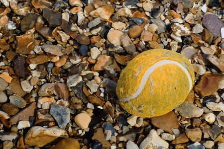 kaput: washed-up deteriorated tennis ball on the beach