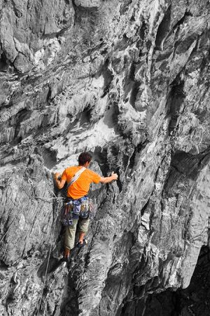 colorized: A climber clad in bright orange colour on a B&W rock, good background for