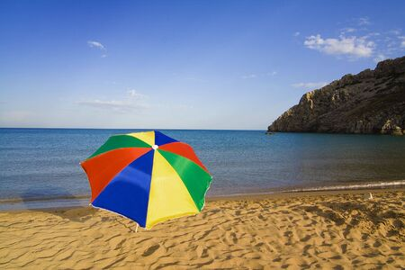 tsampika: A colourful beach umbrella on an empty Tsambika beach on Rhodes Island, Greece