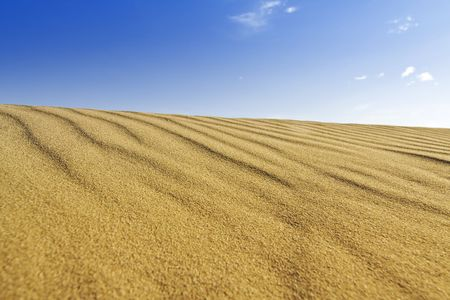 Background of golden sand dune and blue sky photo