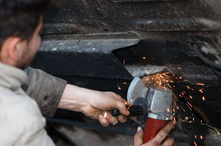 Worker grinding a metal part of vehicle, man on work                                 photo