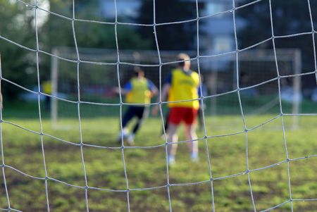 arbitrate: Soccer players in front of net, close-up focus on net