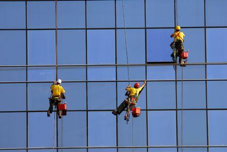 Men washing windows at height, modern skyscraper