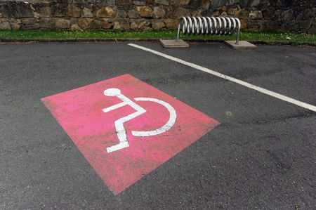 Red colored handicap sign on the parking lot photo