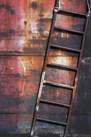backstairs: Old rusty metal ladder, vertical image, diagonal composition