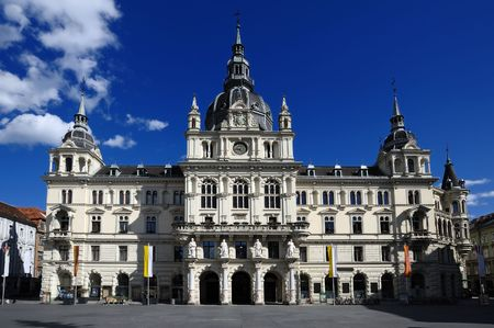 Graz city hall, main facade view with dark blue sky and white clouds