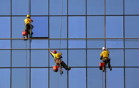 Men washing windows at height, modern skyscraper