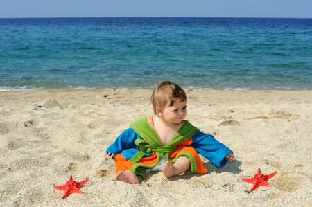 Adorable baby girl playing with red sea stars on the beach Stock Photo