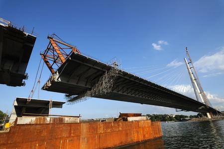 Bridge construction, lifting last segment to the position Stock Photo