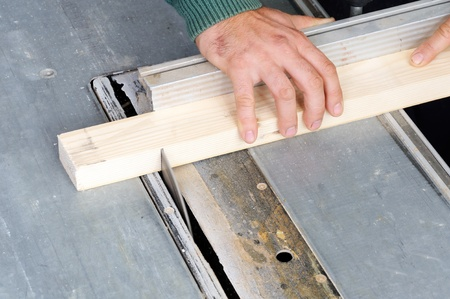 build buzz: Carpenter cutting wood on electric saw, focus is on the blade of the tool