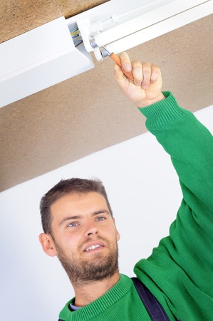 Electrician fixing ceiling light, man on work series photo