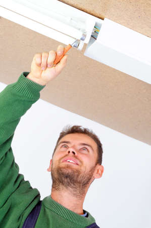 Real handsome electrician fixing ceiling light, man on work series photo