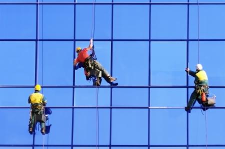 Washers wash the windows of modern skyscraper Reklamní fotografie