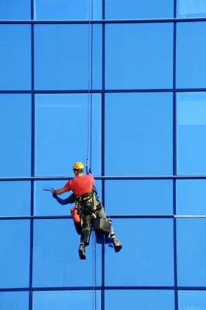 personal de limpieza: Lavadora lavar las ventanas de los rascacielos modernos, el trabajo de alto riesgo Foto de archivo
