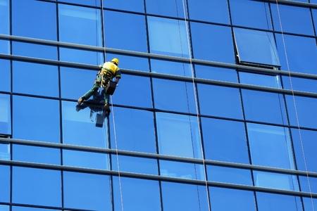 Washer wash the windows of modern skyscraper, high risk work photo