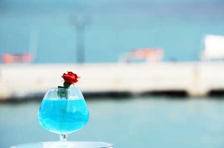 ionio: Red rose against blury harbore in Parga, Greece Stock Photo