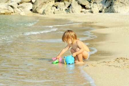ionio: Young and happy toddler girl playing with her bucket at the beach Stock Photo