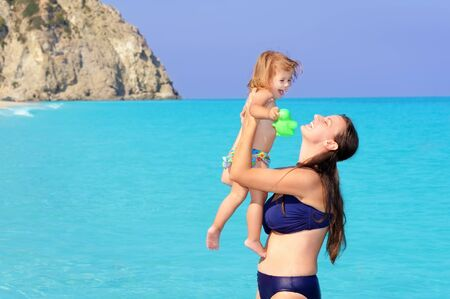 ionio: Happy mother with her daughter on the beach, summer vacation concept