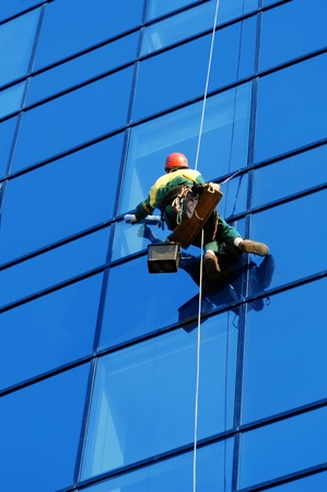 Washer wash the windows of modern skyscraper, high risk work