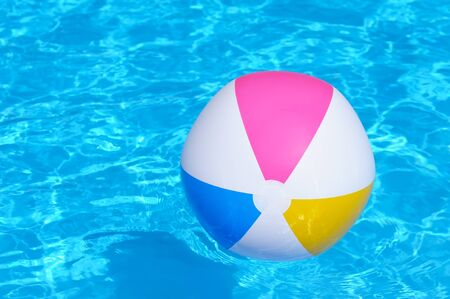 multy: An inflatable multy colored plastic ball in a shiny blue swimming pool  Stock Photo