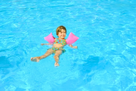 Smiling toddler girl learning to swimm in the swimming pool