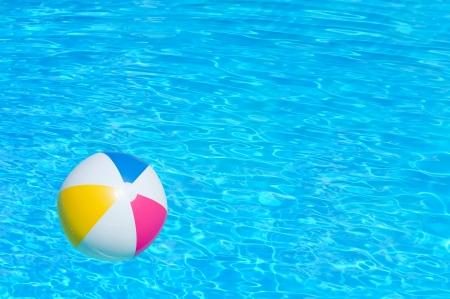 Bola colorida inflable flotando en una piscina Foto de archivo - 24178676