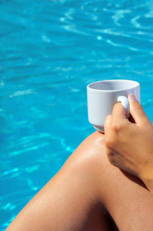 Closeup image of woman legs behind swimming pool, vacation concept Stock Photo