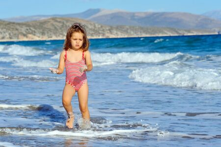 sithonia: Smiling toddler girl running at beach