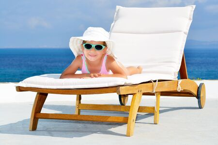 sithonia: Adorable toddler girl relaxing on sunbed Stock Photo