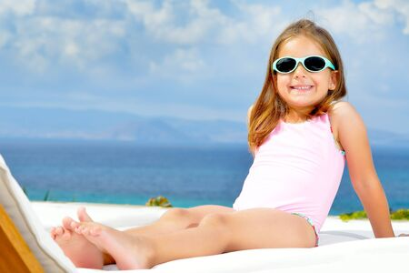 kyklades: Adorable toddler girl relaxing on sunbed Stock Photo