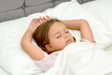 girls night: Adorable little girl sleeping in a bed Stock Photo