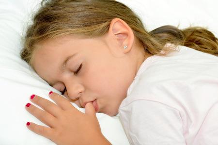 Adorable little girl sleeping in a bed Reklamní fotografie