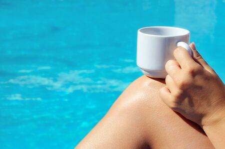Closeup image of real attractive female beauty holding cup of coffee near swimming pool photo