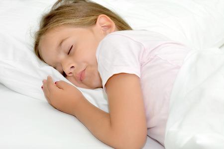 dormir: Adorable niña durmiendo en una cama