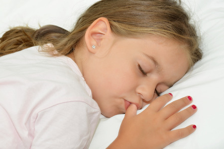 silent night: Adorable little girl sleeping in a bed Stock Photo