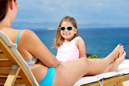 kyklades: Real adorable toddler girl relaxing on the sunbed Stock Photo