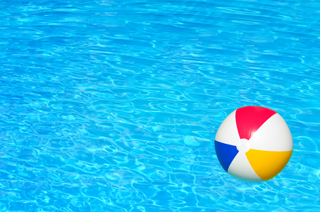 furlough: Colorful inflatable ball floating in swimming pool Stock Photo